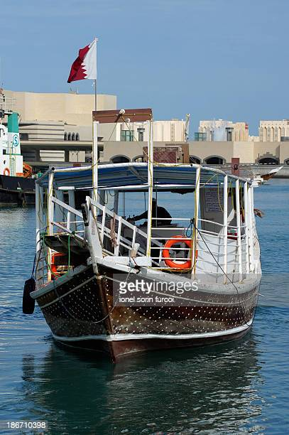 CONTENT] Traditional boat called Dhow sailing through the coastal waters of Doha Qatar