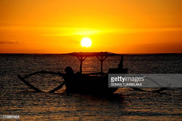 A traditional boat moors during sunset at a beach in the Kuta area of resort island Bali on July 29 2013 The beauty of Bali allures thousands of...