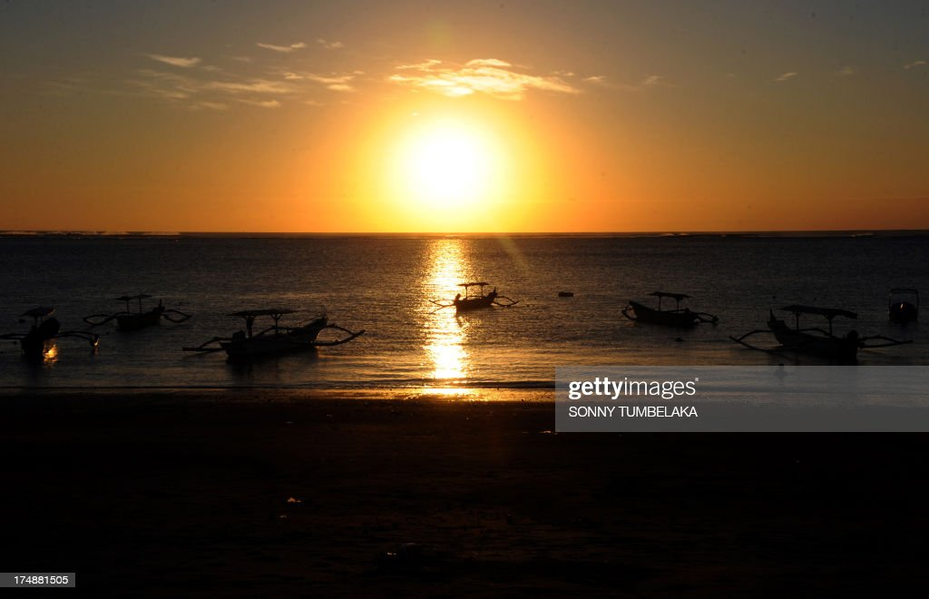 Traditional boats moor during sunset at a beach in the Kuta area of resort island Bali on July 29, 2013