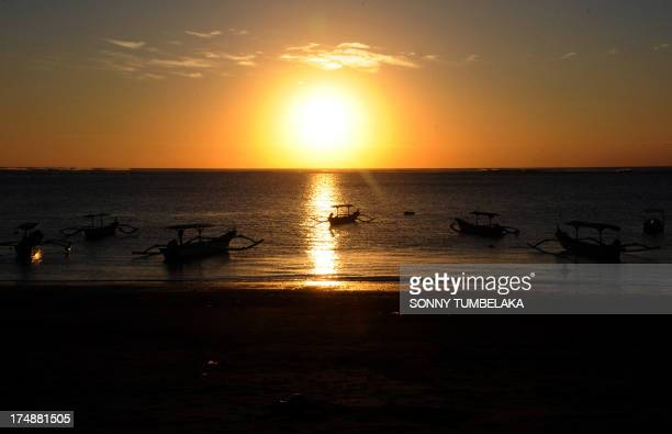 Traditional boats moor during sunset at a beach in the Kuta area of resort island Bali on July 29 2013 The beauty of Bali allures thousands of...