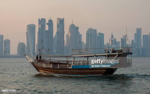 Traditional boats with Doha skyline in the background at sunrise, Qatar