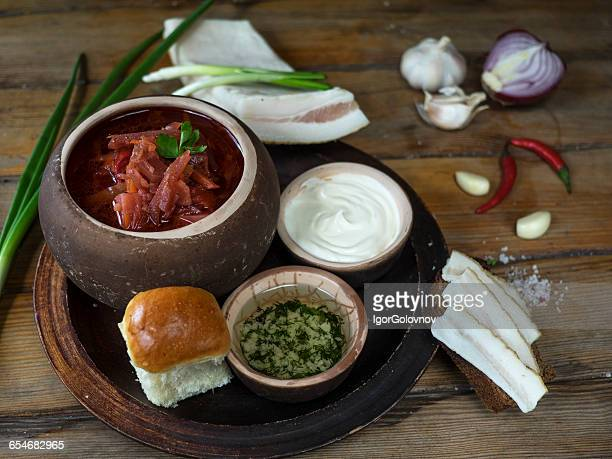 Traditional borscht soup with bread, sour cream and chopped herbs