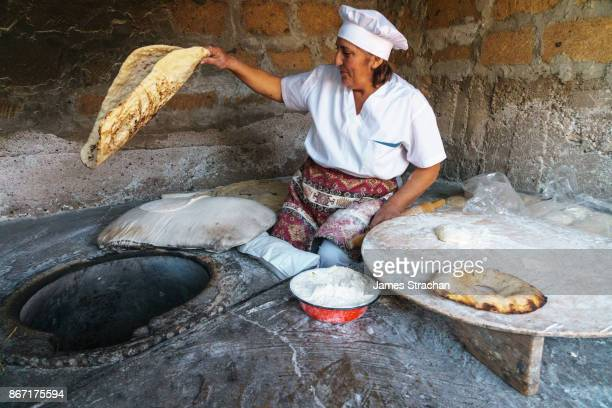 Traditional breadmaker pulling fresh lavash bread out of her clay oven, (smaller bread is bokon), Yerevan, Armenia (Model Release)