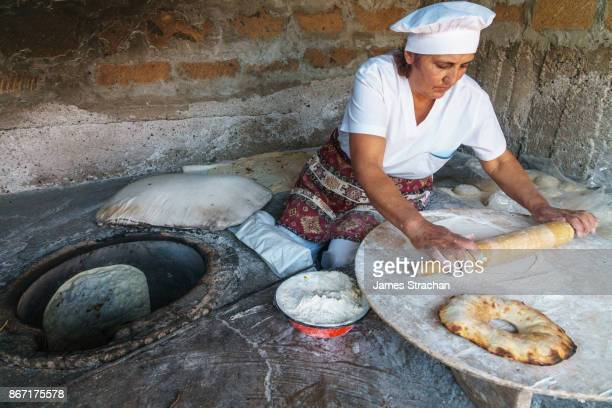 Traditional breadmaker rolling lavash bread before placing into clay oven to bake, (smaller bread is bokon), Yerevan, Armenia (Model Release)