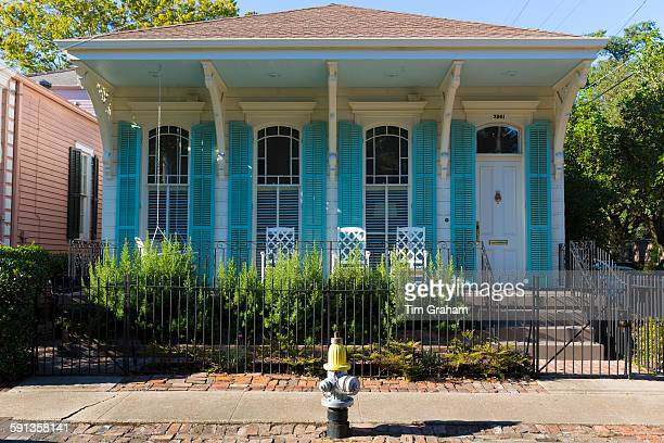 Traditional bright color clapboard cottage house in the Garden District of New Orleans Louisiana USA