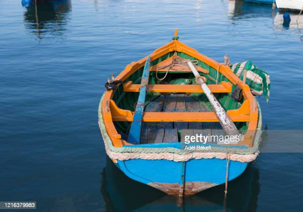 traditional brightly painted fishing boat in the harbour (marsaxlokk malta) - marsaxlokk stock pictures, royalty-free photos & images