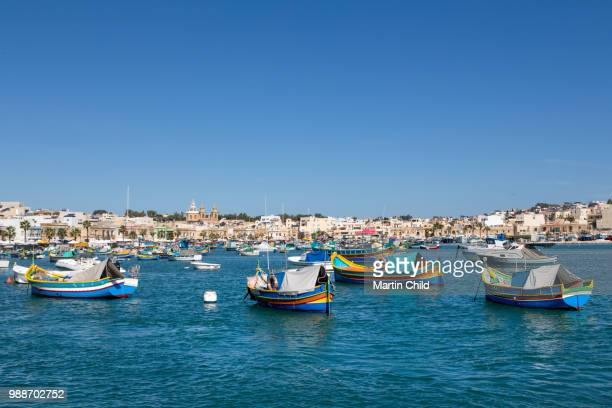 traditional brightly painted fishing boats in the harbour at marsaxlokk, malta, mediterranean, europe - marsaxlokk stock pictures, royalty-free photos & images