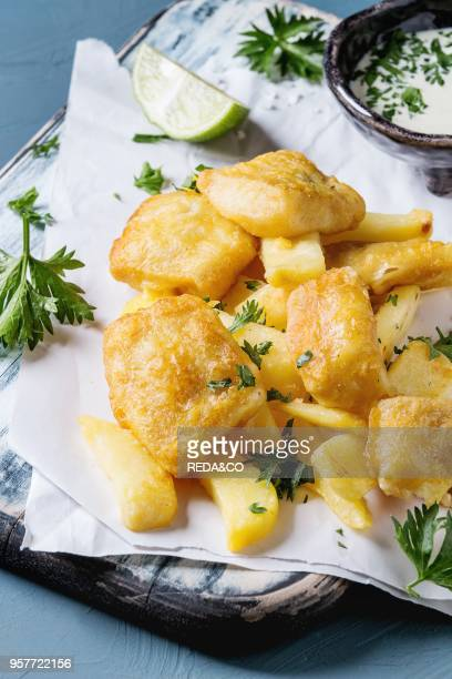 Traditional british fast food fish and chips Served with white cheese sauce lime parsley on white paper and black serving board over blue concrete...