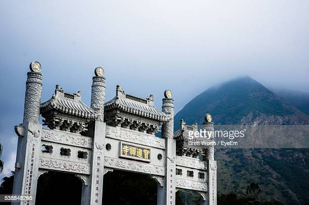 Traditional Built Structure By Mountain Against Sky