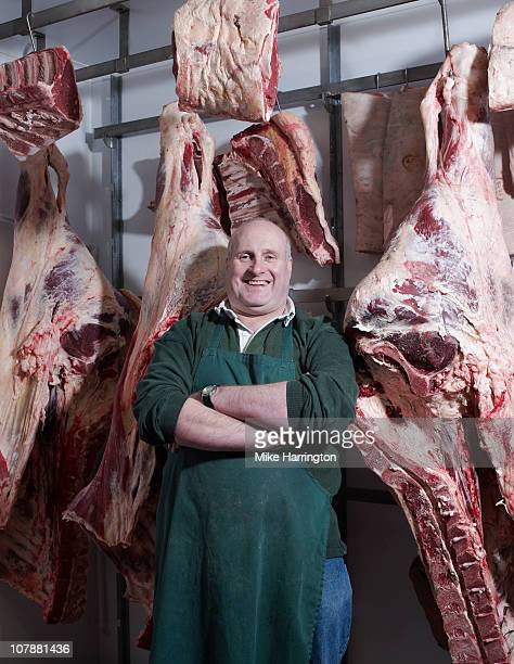 Traditional Butcher standing by chilled meat