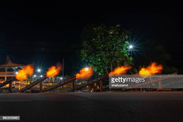 traditional cannon made from coconut palm tree light up during the celebration of eid-mubarak. - shaifulzamri stock pictures, royalty-free photos & images