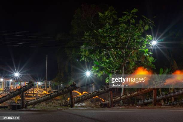 traditional cannon made from coconut palm tree light up during the celebration of eid-mubarak. - shaifulzamri photos et images de collection
