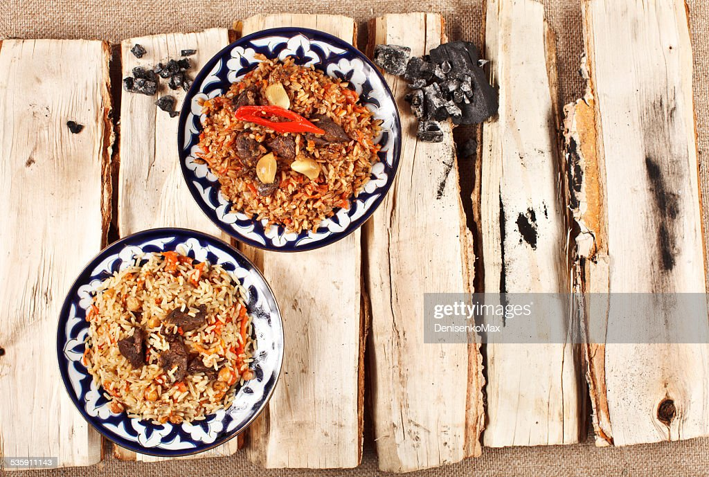 traditional central asia pilaw in uzbek plate on logs : Stock Photo