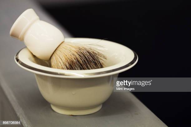 a traditional ceramic shaving bowl and shaving brush. - shaving brush stock photos and pictures