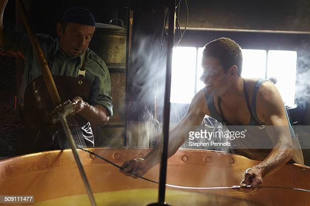 traditional cheese makers stirring milk - フリブール州 ストックフォトと画像
