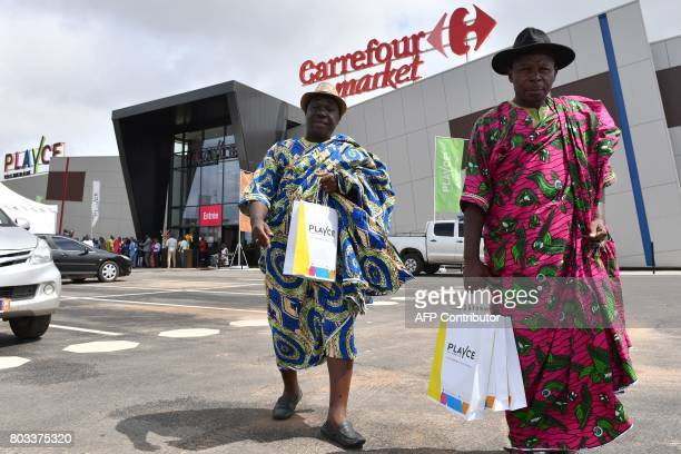Traditional chief holds shopping bag during the inauguration of a new shopping mall launched by CFAO Retail on June 29, 2017 in Abidjan. / AFP PHOTO...
