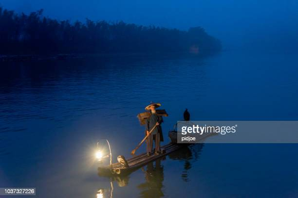traditional chinese 75 year old senior fisherman in traditional clothes and bamboo hat on his wooden fishing raft with two cormorants fishing on the li river in the early morning fog light at sunrise. shot at xing ping, close to the city of yangshuo count - 70 year old man stock pictures, royalty-free photos & images