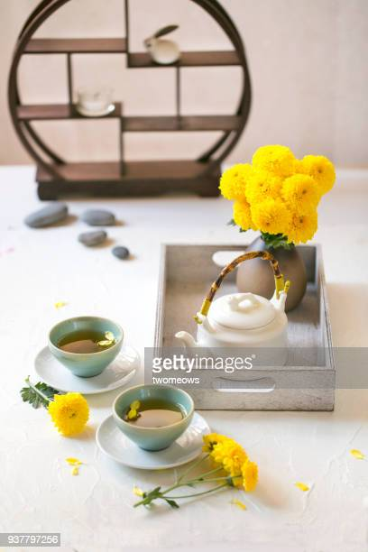Traditional Chinese chrysanthemum tea set on white table top.