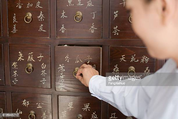 Traditional Chinese doctor opening medicine cabinet drawer
