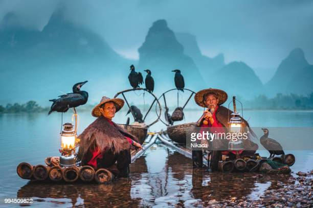traditional chinese fishermen taking a break on bamboo raft - tradition stock pictures, royalty-free photos & images