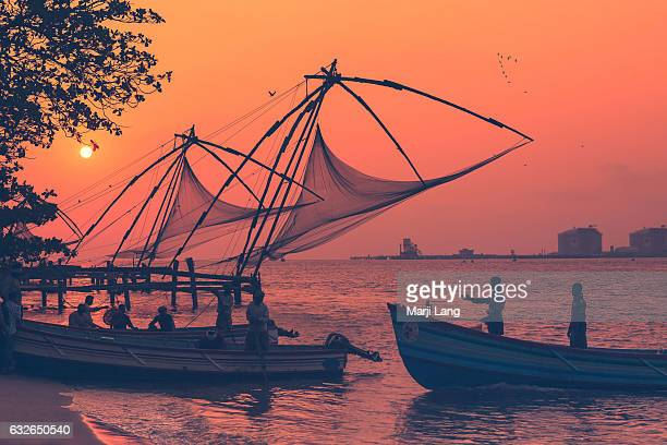 Traditional Chinese fishing nets at sunset in Kochi and fishermen coming back on their boats Kerala India