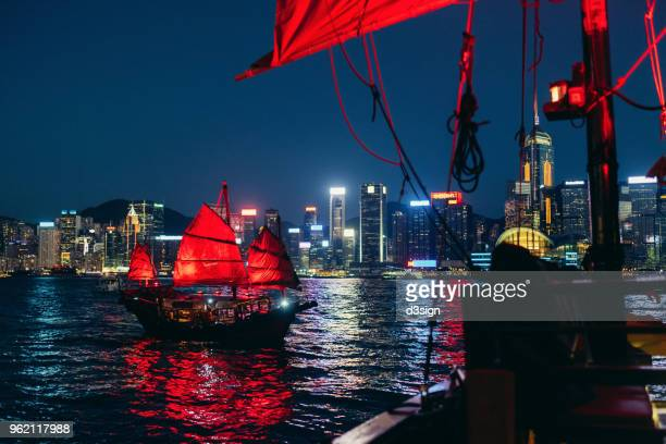 traditional chinese junk boat with vibrant red flags sailing across victoria harbour against illuminated city skyline of hong kong - victoria harbour hong kong stockfoto's en -beelden
