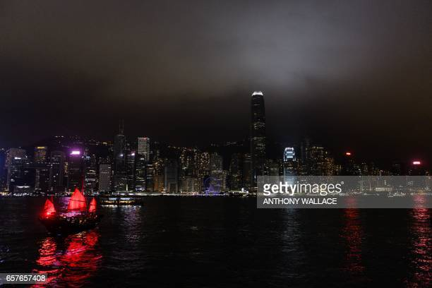 TOPSHOT A traditional Chinese junk sails in Victoria Harbour in front of the skyline after the building lights were switched off for the Earth Hour...
