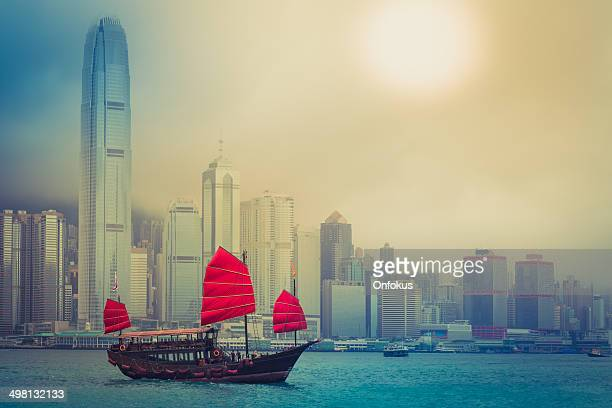 traditional chinese junkboat sailing across victoria harbour, hong kong - hong kong victoria harbour stock pictures, royalty-free photos & images