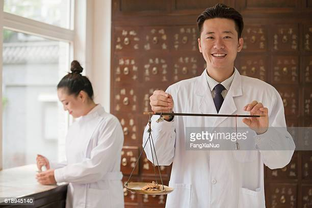 Traditional Chinese medicine doctor using scale