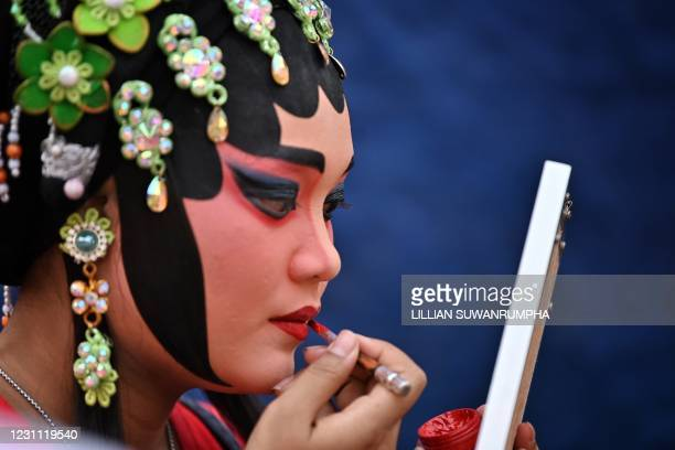 Traditional Chinese Opera performer from the Sai Yong Hong troupe applies lipstick backstage before a performance on the first day of the Lunar New...