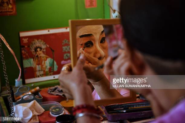 Traditional Chinese Opera performer from the Sai Yong Hong troupe applies eye makeup backstage before a performance on the first day of the Lunar New...