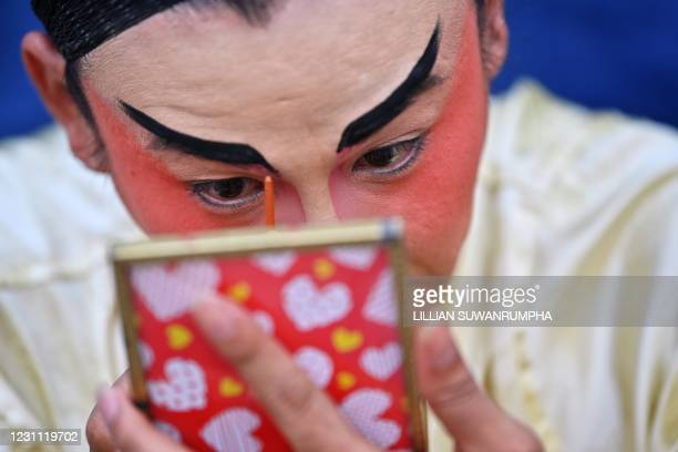 Traditional Chinese Opera performer from the Sai Yong Hong troupe applies makeup backstage before a performance on the first day of the Lunar New...