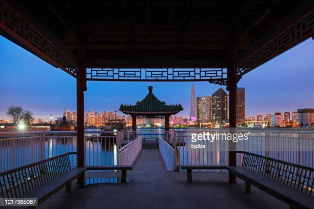 traditional chinese pavilions and modern buildings in the evening - tianjin stock pictures, royalty-free photos & images