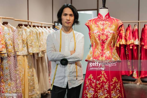 traditional chinese wedding dress designer in his studio - fashion industry stock pictures, royalty-free photos & images