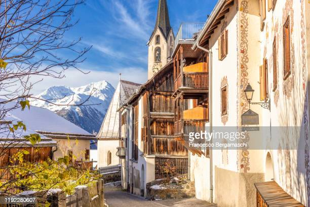 traditional church and wood houses in the alpine village. - guarda switzerland stock pictures, royalty-free photos & images