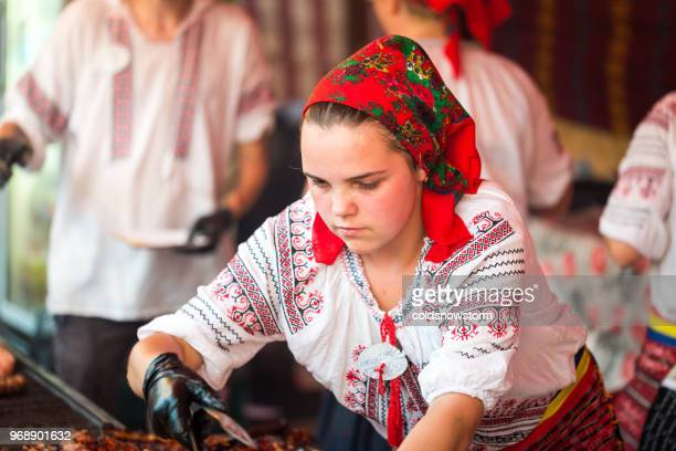 traditional clothing romanian woman serving food on market stall - transylvania stock pictures, royalty-free photos & images