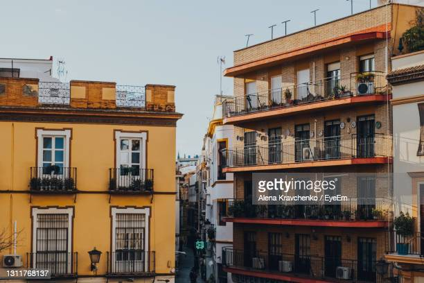 traditional colourful buildings with balconies on a street in seville, spain. - seville stock pictures, royalty-free photos & images