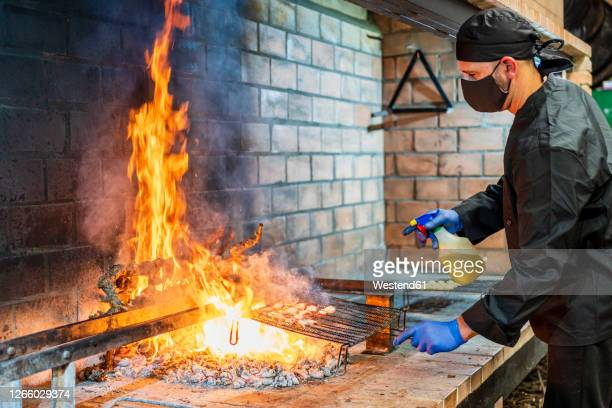 traditional cooking of seafood on grill in restaurant kitchen, chef wearing protective mask - in flames i the mask stock pictures, royalty-free photos & images