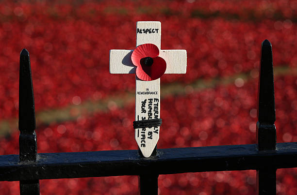 A traditional cross of remembrance is placed on railings surrounding the 'Blood Swept Lands and Seas of Red' installation in the moat of the Tower of...