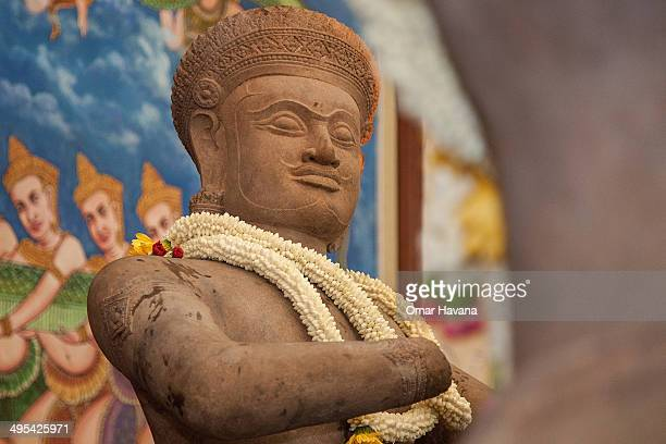 A traditional crown of flowers sits on the neck of the Bhima statue returned by the Norton Simon Museum to Cambodia during a handover ceremony at the...