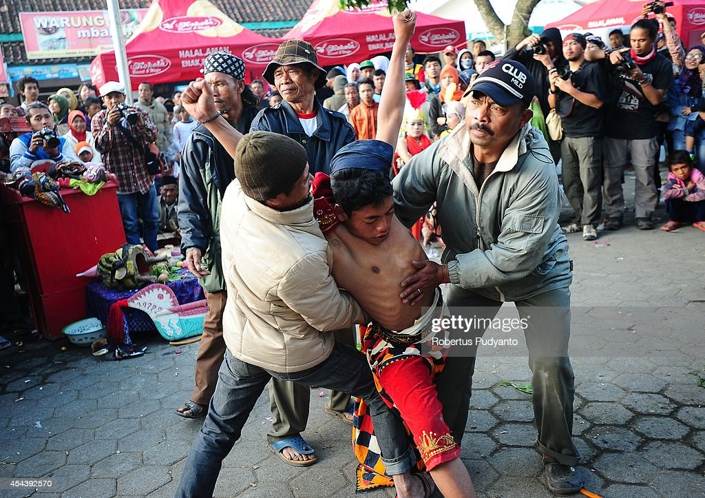 A traditional dancer goes into a trance and is assisted while he performs during Dieng Cultural Festival 2014 on August 30, 2014 in Dieng, Java, Indonesia. The Dieng Culture Festival is an annual event presenting a variety of arts and culture culminating with a hair trimming ritual ceremony of dreadlocked children, known as the Ruwatan Rambut Gimbal.
