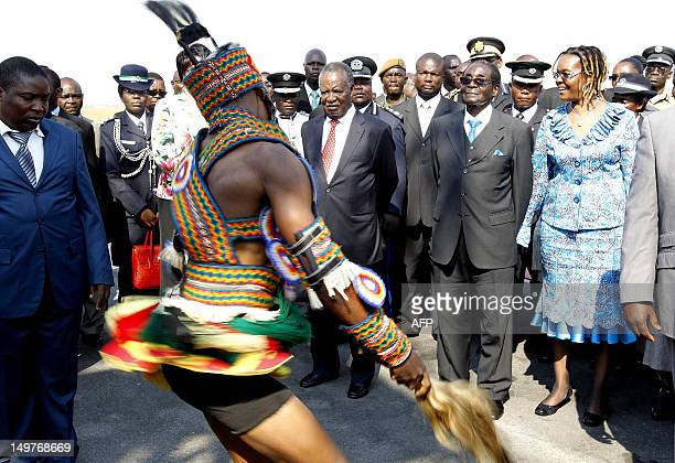 A traditional dancer performs for Zimbabwean President Robert Mugabe flanked by his wife Grace and Zambian President Michael Sata on August 3 2012 at...