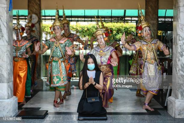 Traditional Dancers at the Erawan shrine, a popular tourist site perform while wearing face shields next to a woman offering prayers, wearing a face...