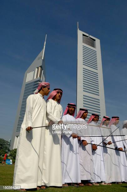 Traditional dancers behind Emirates Towers.