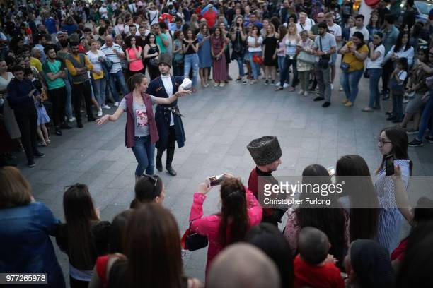 Traditional dancers entertain World Cup football fans as they enjoy the party atmosphere on Nikolskaya Street near Red Square on June 17 2018 in...