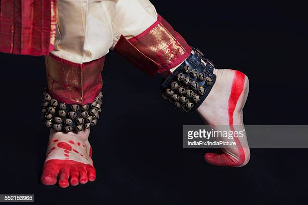 Traditional dancers feet performing Bharatanatyam on black background