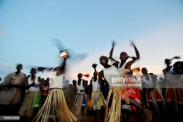 Traditional dancers jump and smile after their performance during a political rally for opposition presidential candidate Agathon Rwasa, in the south...