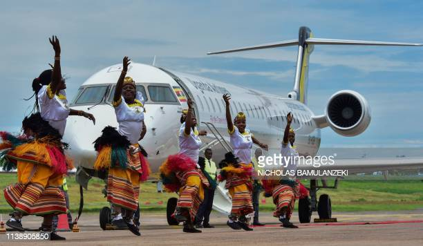 Traditional dancers perform a routine in front of a newly acquired Uganda Airlines Bombardier CRJ900 aircraft on the runway at Entebbe Airport on the...
