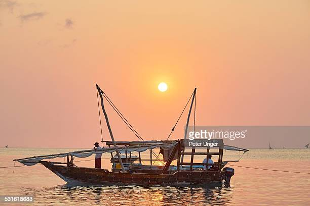 traditional dhow boat moored at beach on sunset - image title stock pictures, royalty-free photos & images