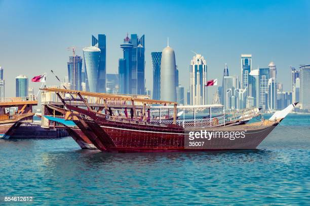 traditional dhow with modern skyline in doha, qatar - qatar stock pictures, royalty-free photos & images